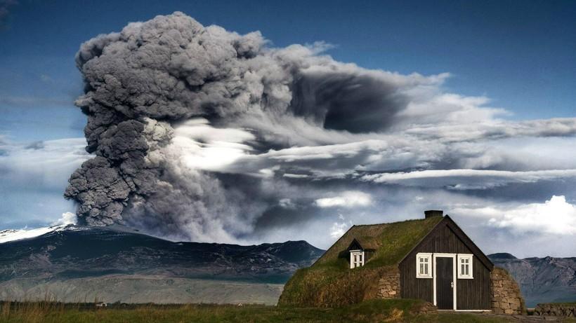 На фото: традиционный исландский дерновый дом на фоне вулкана Эйяфьятлайокудль