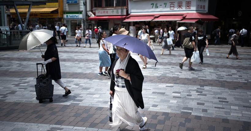 Японцы спасаются от жары под зонтиками